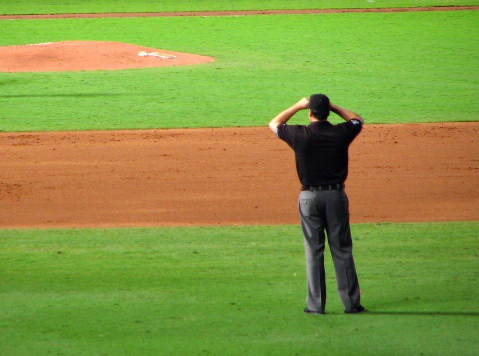A baseball umpire standing on a baseball diamond : Free Stock Photo