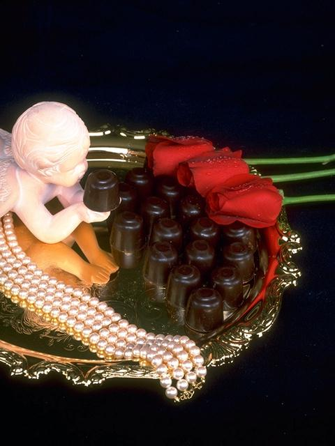 A tray of red rose and chocolate candy with a cupid statue : Free Stock Photo