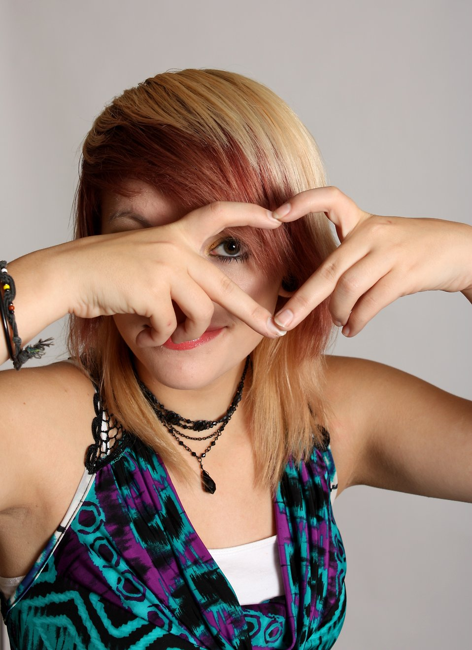 A beautiful young woman making a heart symbol with her hands : Free Stock Photo
