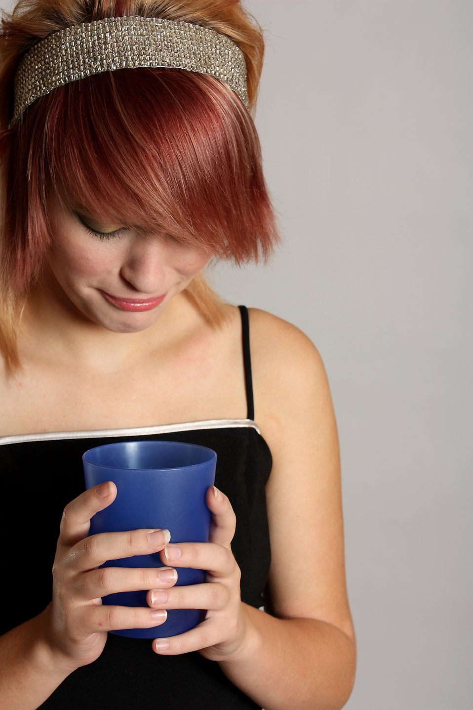 A beautiful girl looking unhappily into a drink in a plastic cup : Free Stock Photo