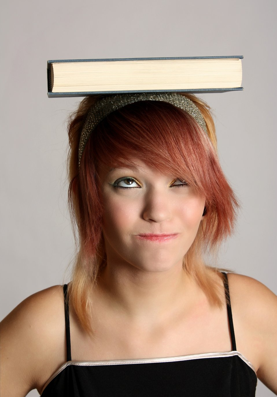 A beautiful young girl balancing a book on her head : Free Stock Photo