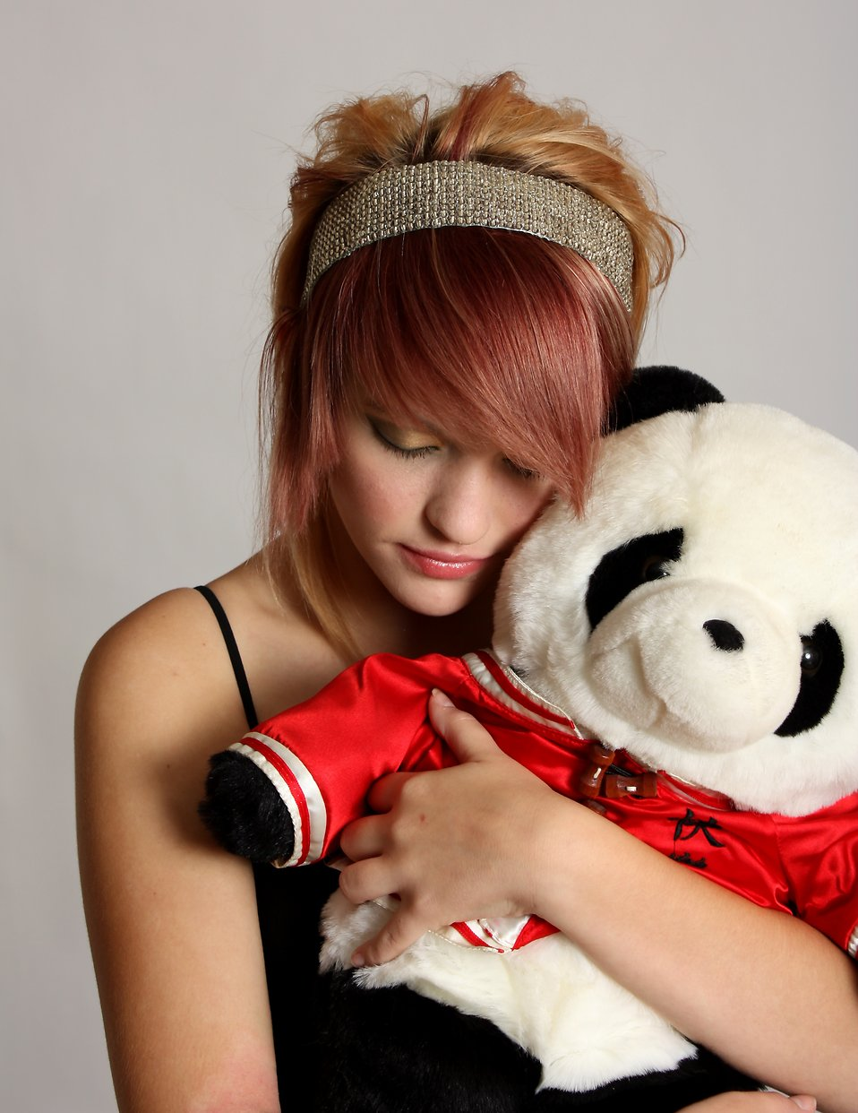 A beautiful young girl holding a stuffed panda bear : Free Stock Photo