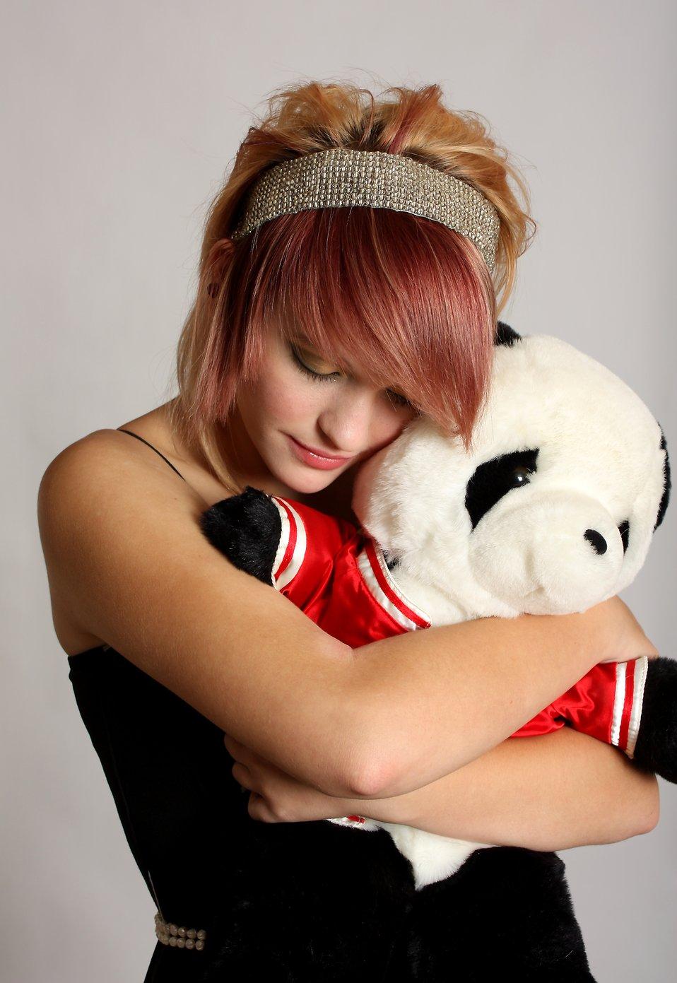 A beautiful young girl holding a stuffed panda bear : Free Stock Photo