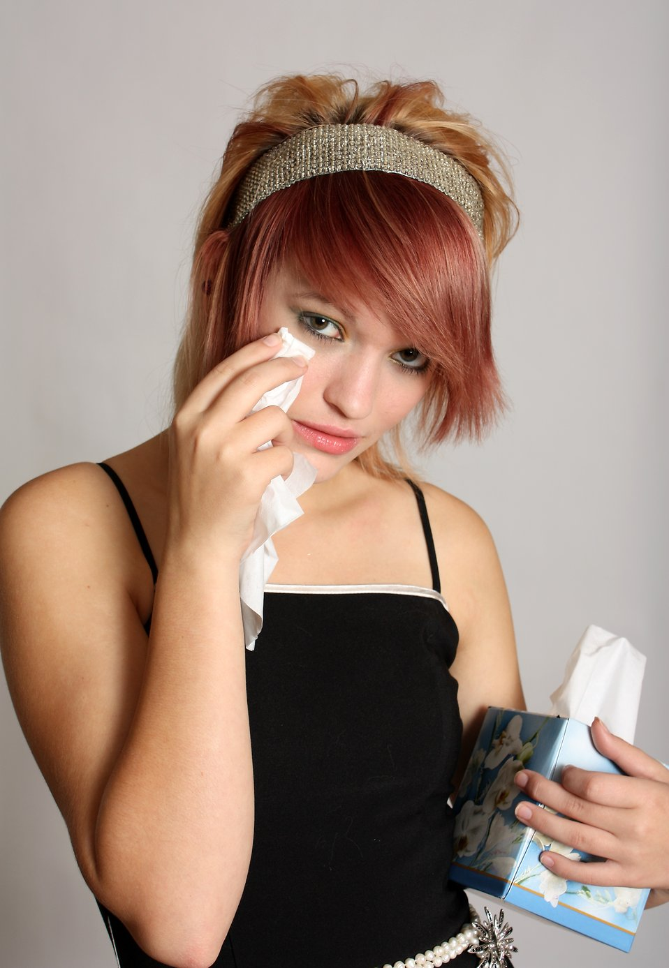 A beautiful young girl crying into a tissue : Free Stock Photo