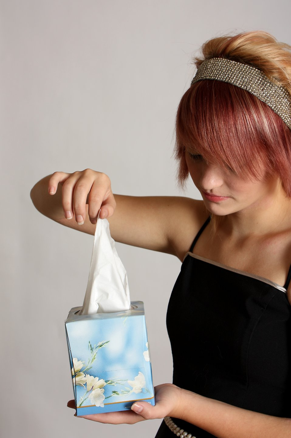 A beautiful young girl holding a box of tissues : Free Stock Photo