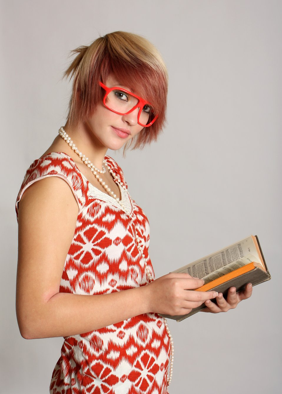 A beautiful smart young girl with glasses reading a book : Free Stock Photo