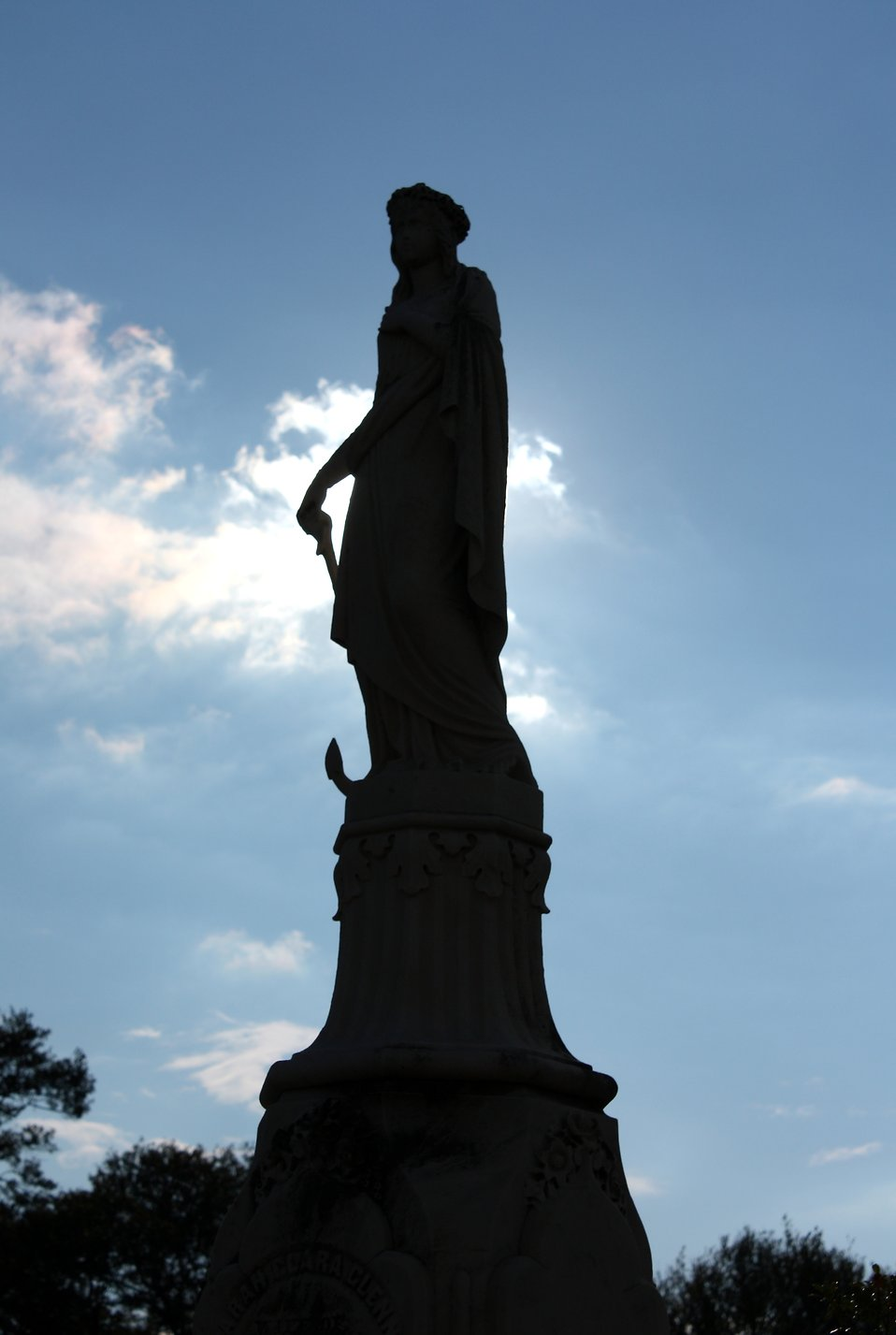 Silhouette of a large statued tombstone at historic Oakland Cemetery in Atlanta, Georgia : Free Stock Photo