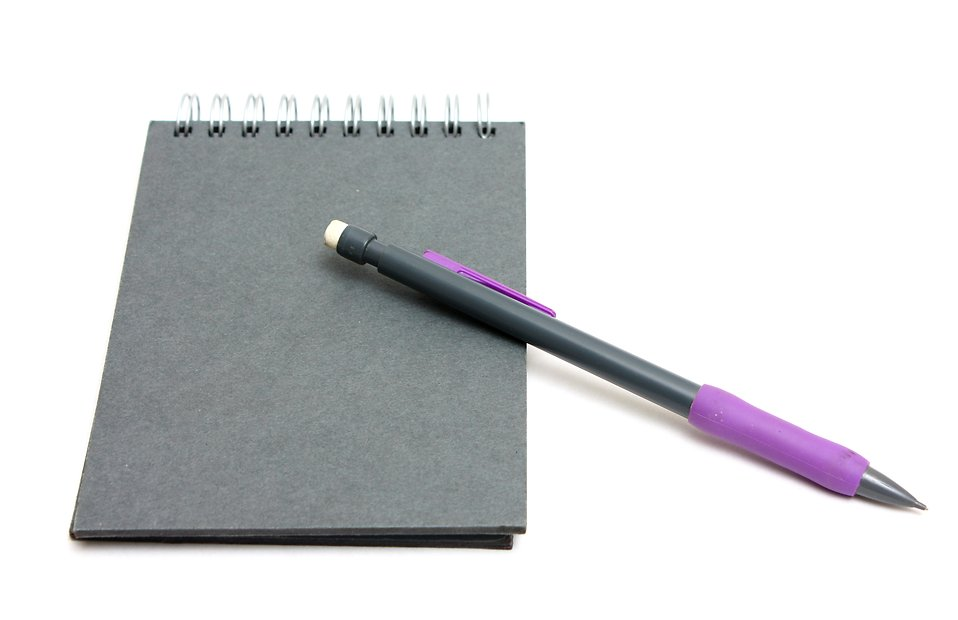 A pad of paper and a pencil isolated on a white background.