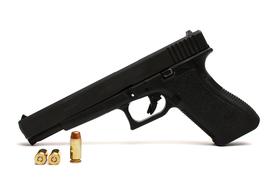 A Glock 24 pistol with ammo on a white background.