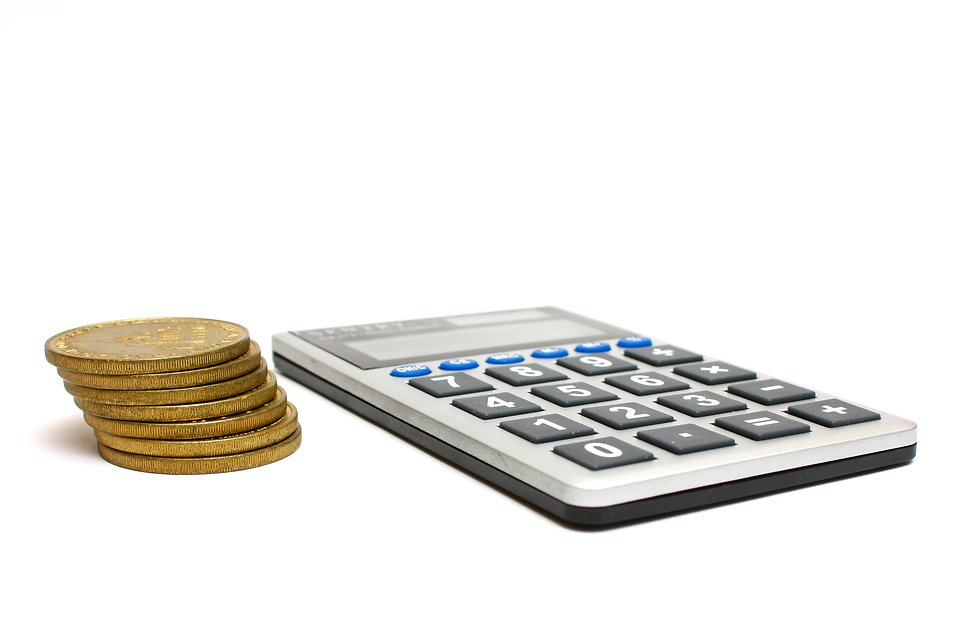 A calculator and a stack of gold coins.