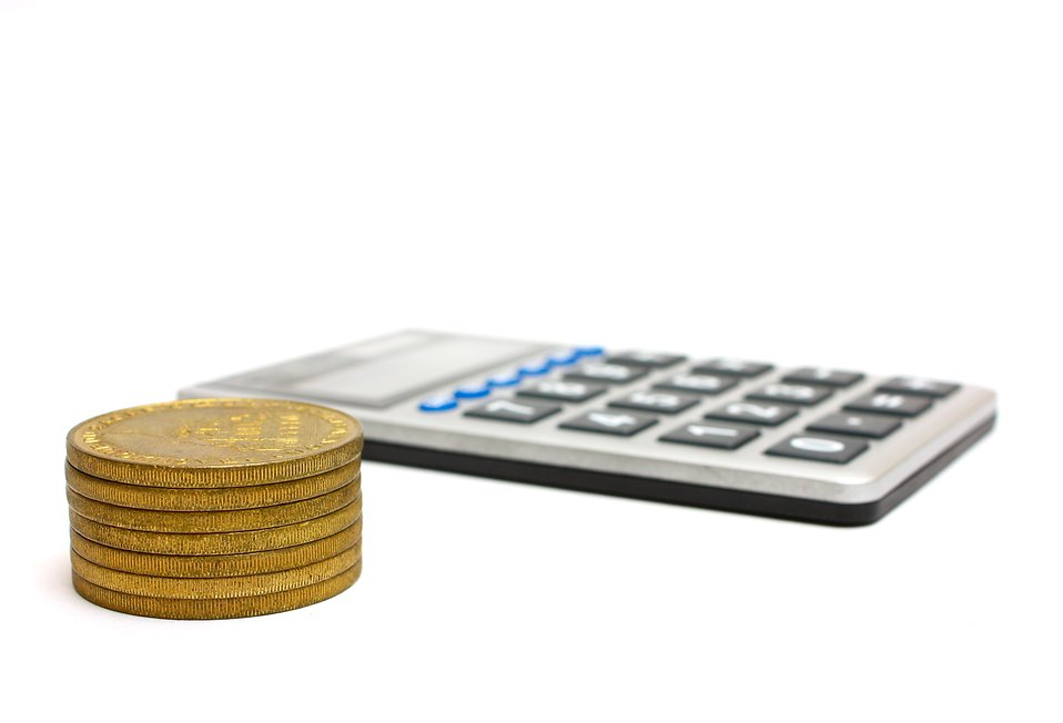 A calculator and a stack of gold coins : Free Stock Photo