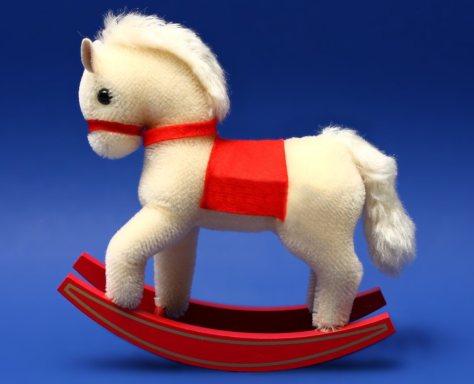 A stuffed rocking horse isolated on a blue background : Free Stock Photo