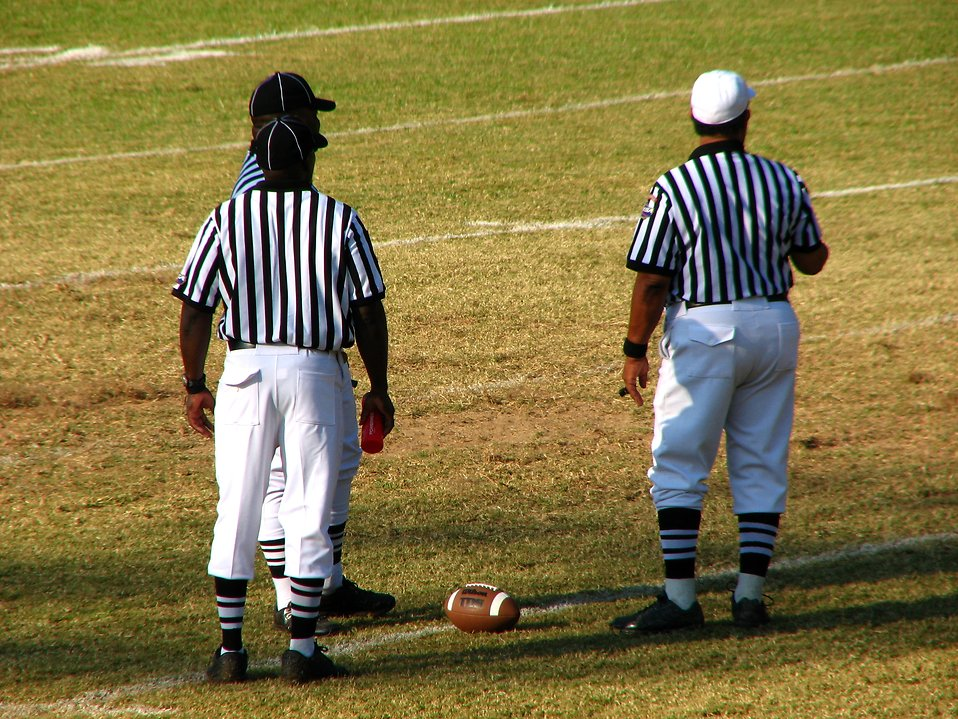 Football referees standing on a field : Free Stock Photo