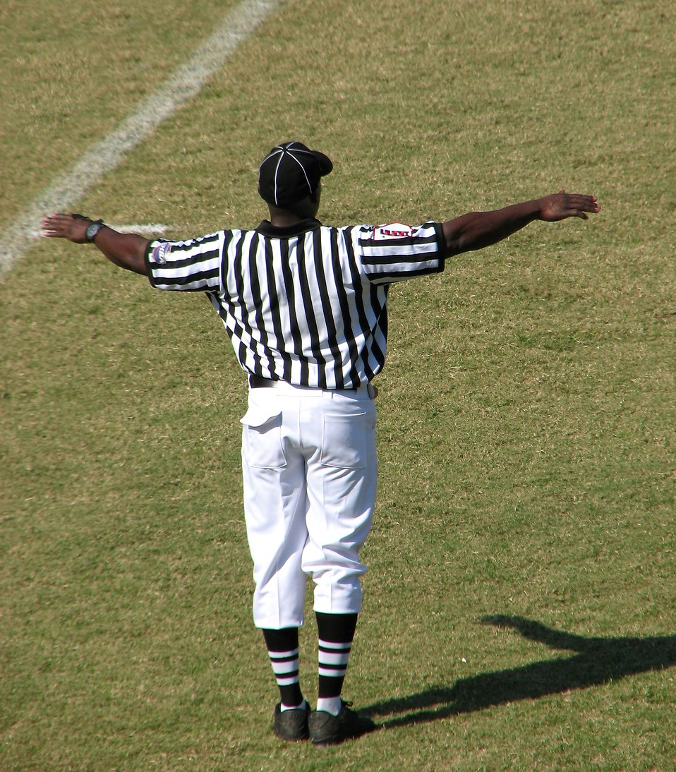 A football referee on a field making an incomplete pass signal : Free Stock Photo