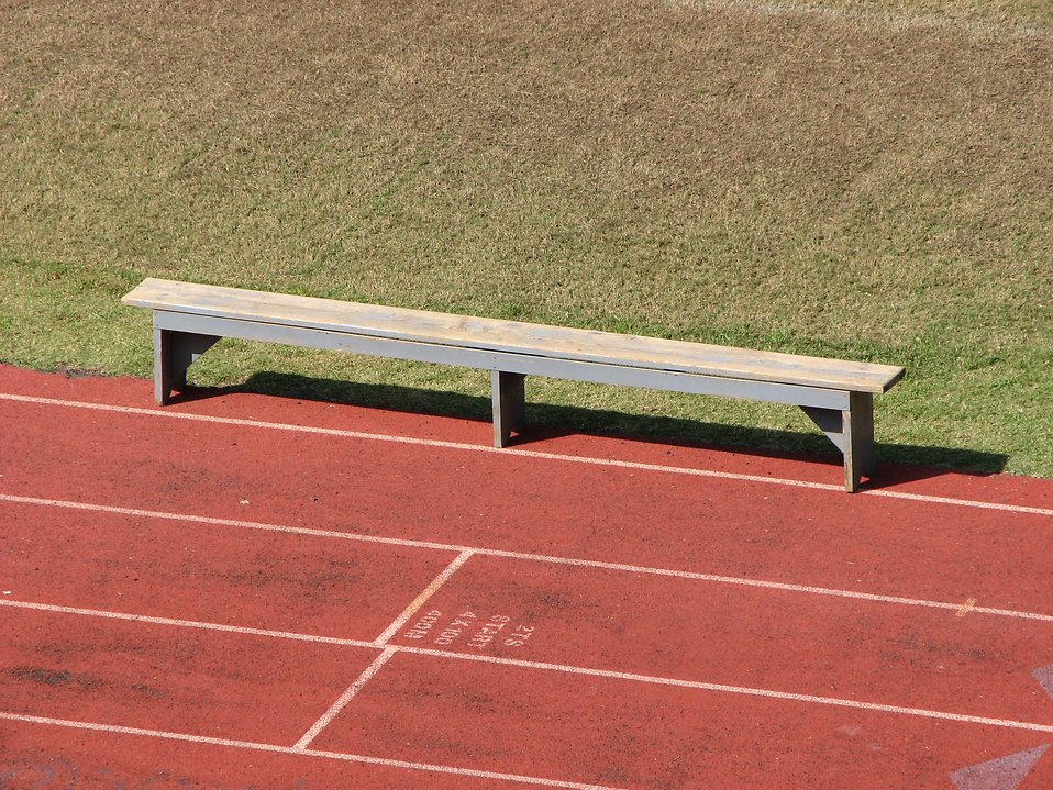 An empty bench on a track field : Free Stock Photo