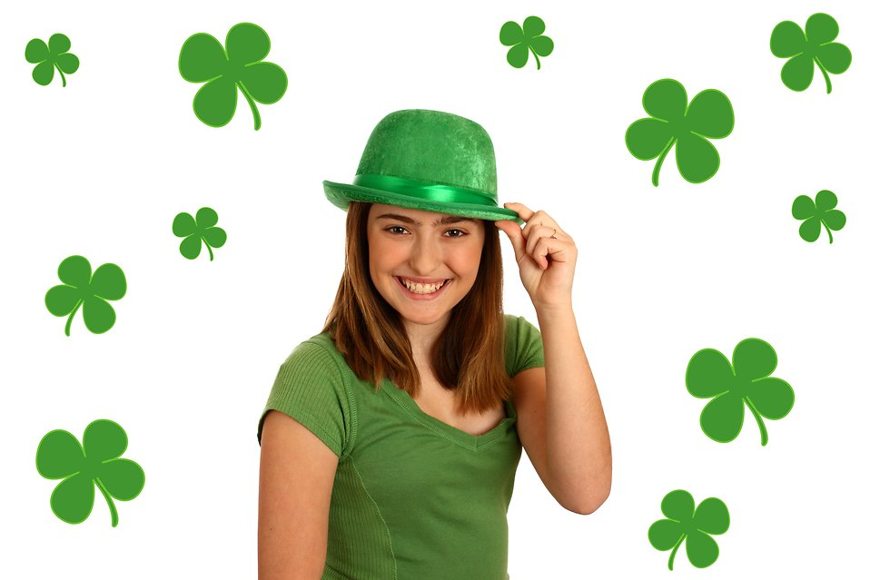 A cute young girl dressed up for Saint Patrick's Day with a green hat surrounded by shamrocks : Free Stock Photo