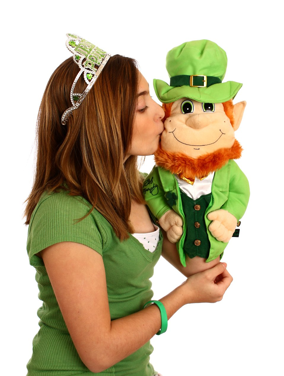 A cute young girl dressed up for Saint Patrick's Day kissing a leprechaun puppet : Free Stock Photo
