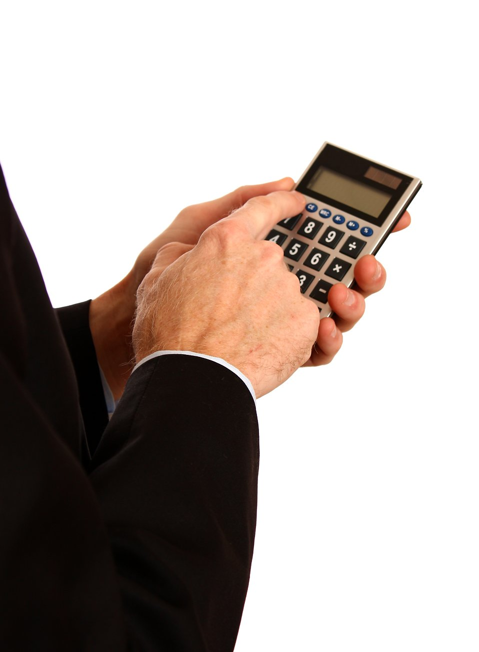 A young businessman in a suit using a calculator.