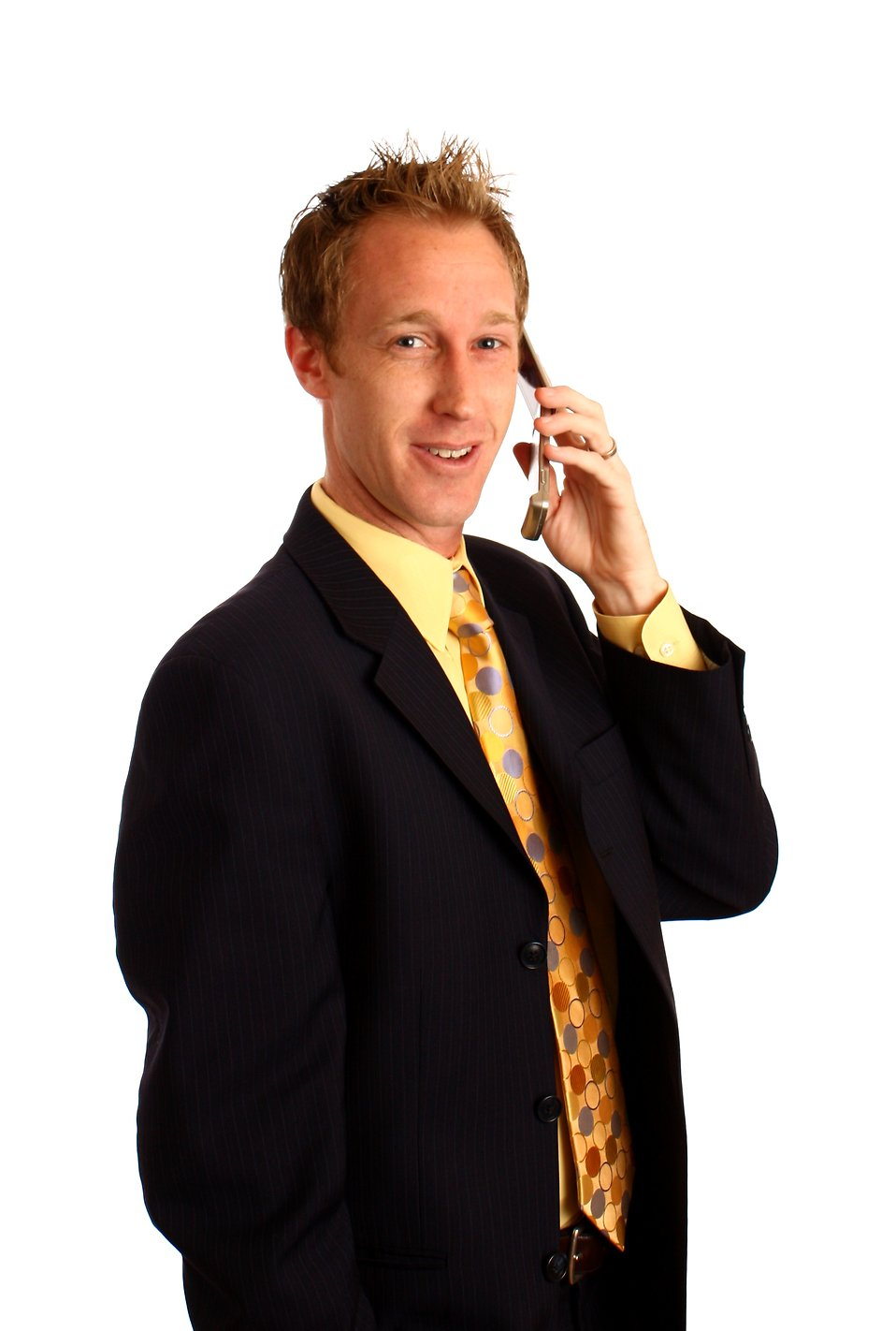 A young businessman in a suit talking on a cell phone : Free Stock Photo