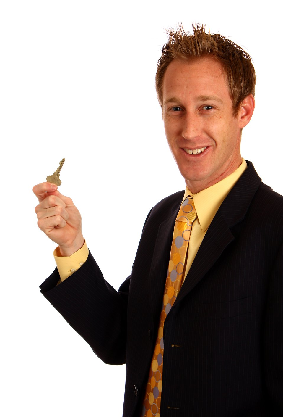 A young businessman in a suit holding a key : Free Stock Photo