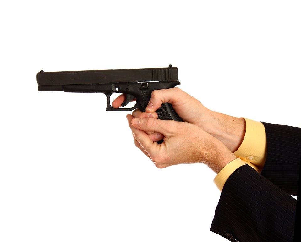 A hand in a business suit holding a pistol : Free Stock Photo
