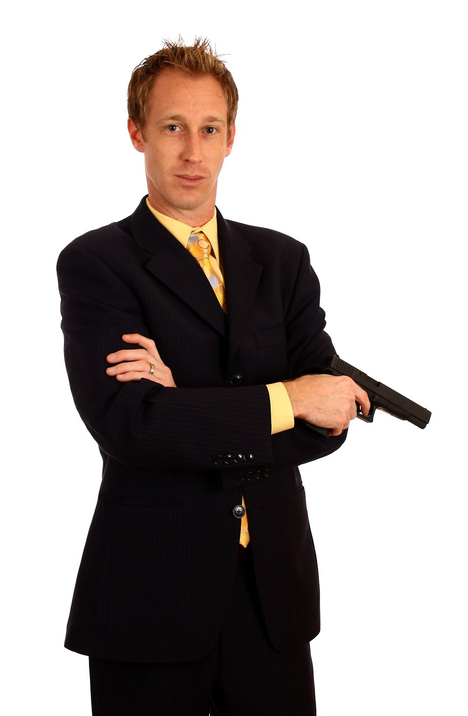 A young businessman in a suit holding a pistol : Free Stock Photo