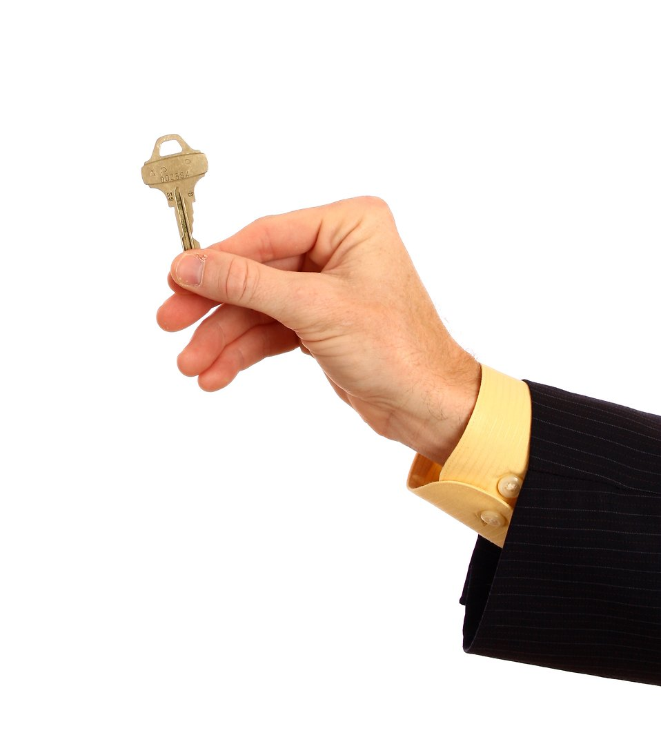 A hand in a business suit holding a key.