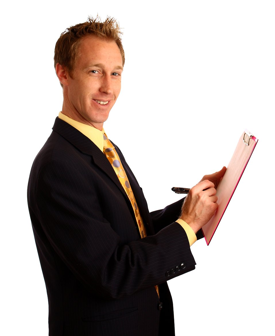 A young businessman in a suit writing on a clipboard : Free Stock Photo