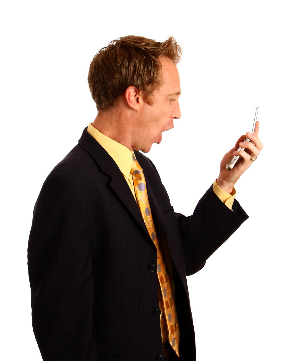 A young businessman in a suit screaming at a cell phone : Free Stock Photo