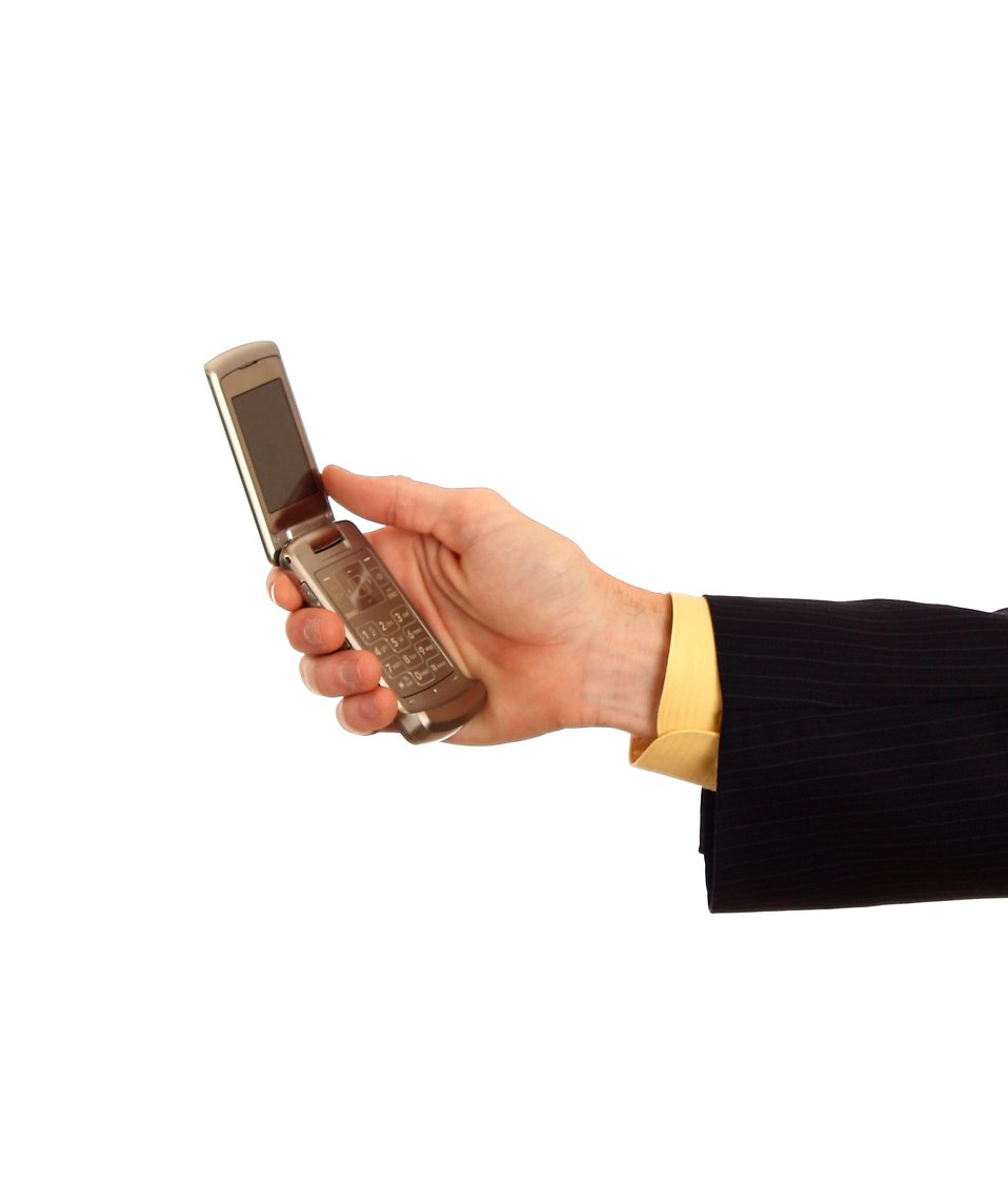 A hand in a business suit holding a cell phone : Free Stock Photo