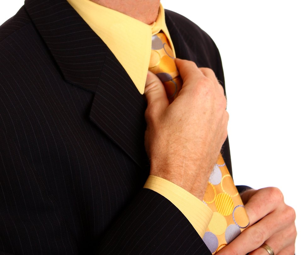 A young businessman in a suit adjusting his tie : Free Stock Photo