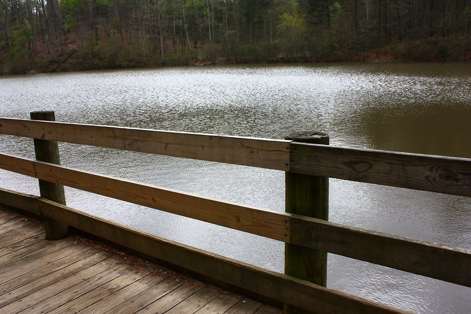 A wooden fence by a lake.