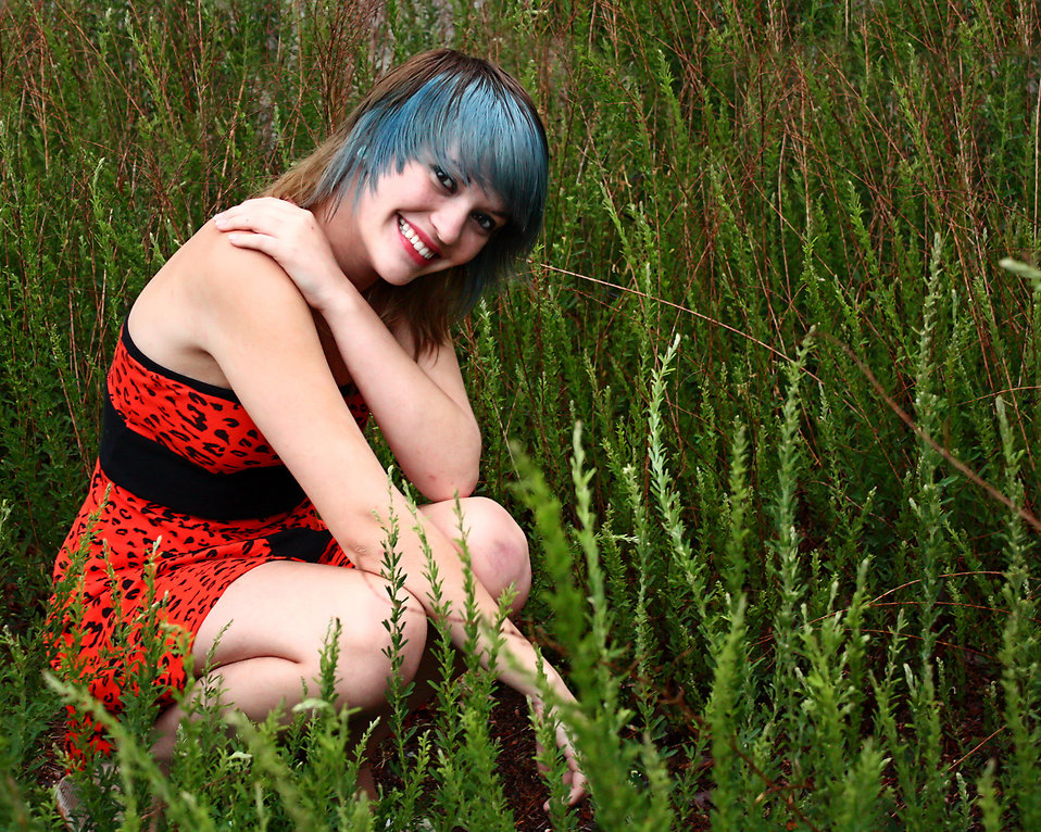 A beautiful young woman posing in a red dress in tall grass : Free Stock Photo