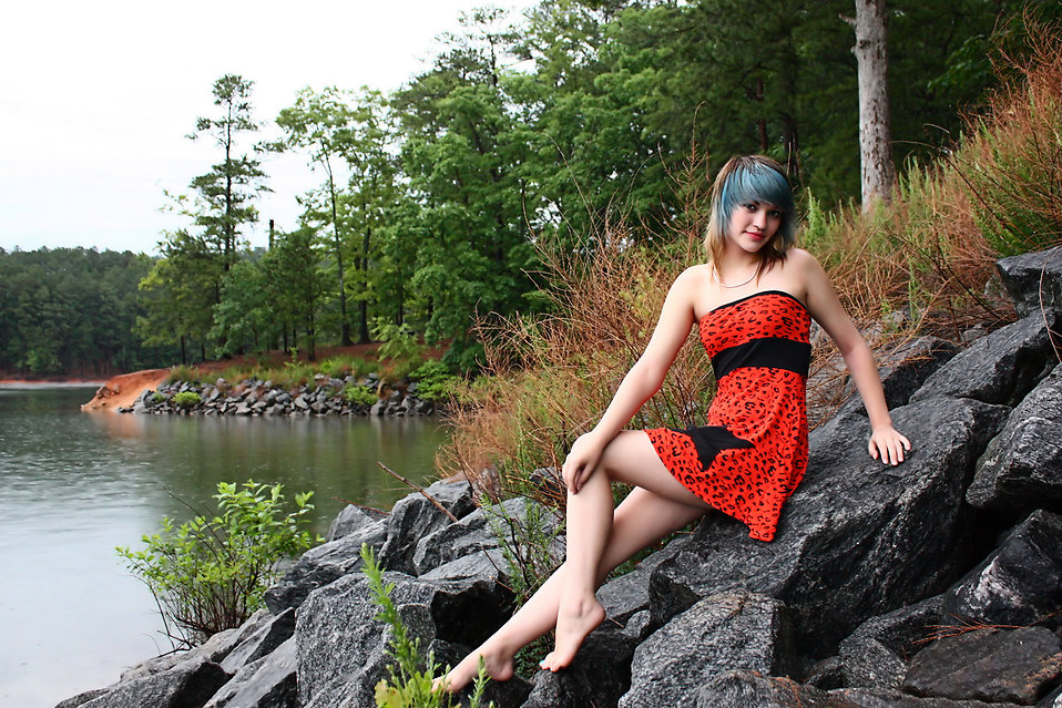 A beautiful young woman posing in a red dress on rocks by a lake.