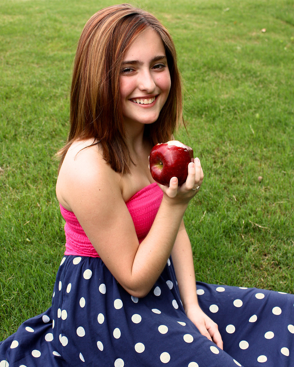 A beautiful young girl holding an apple in the grass : Free Stock Photo