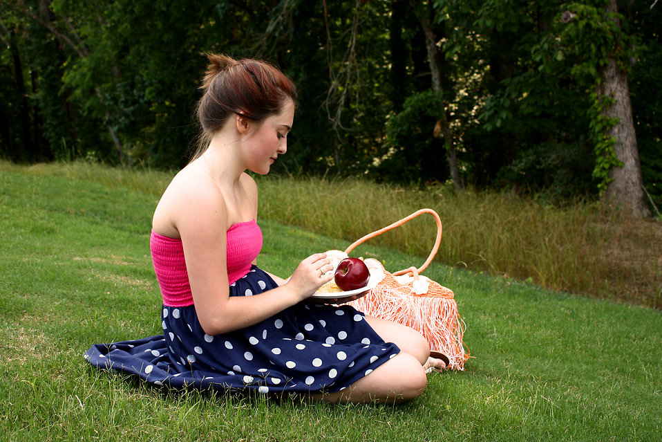 A beautiful young girl having a picnic in the grass : Free Stock Photo