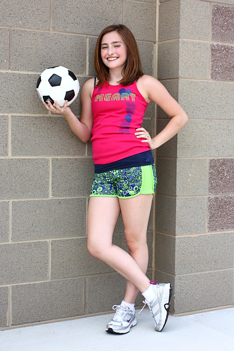 A cute young girl posing with a soccer ball : Free Stock Photo