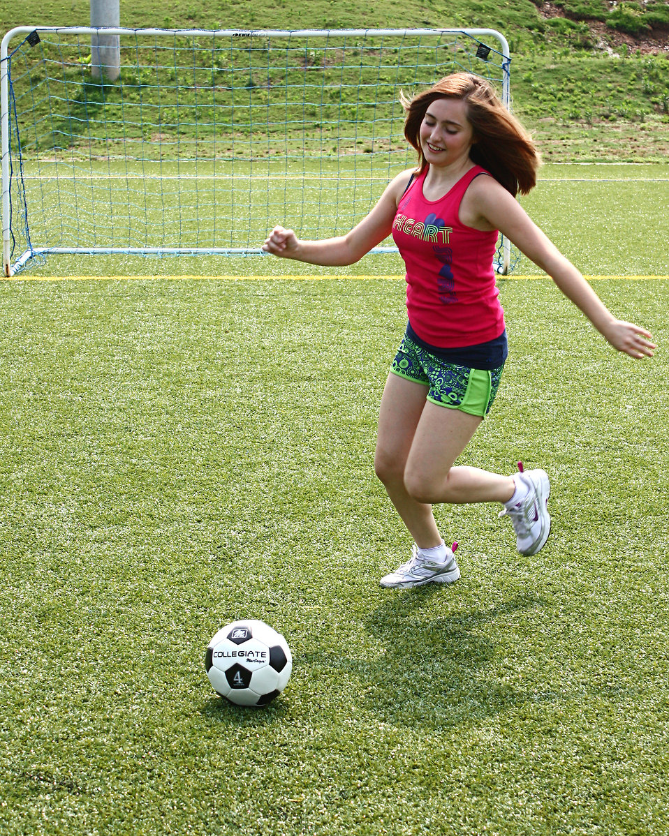 A cute young girl kicking a soccer ball : Free Stock Photo