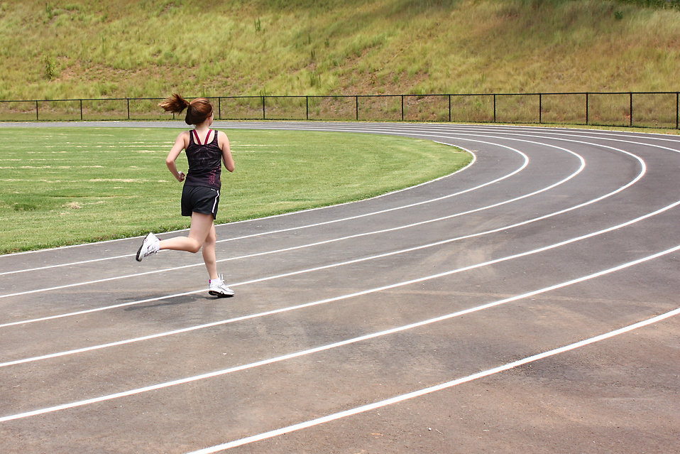 A cute young girl running on a track field : Free Stock Photo