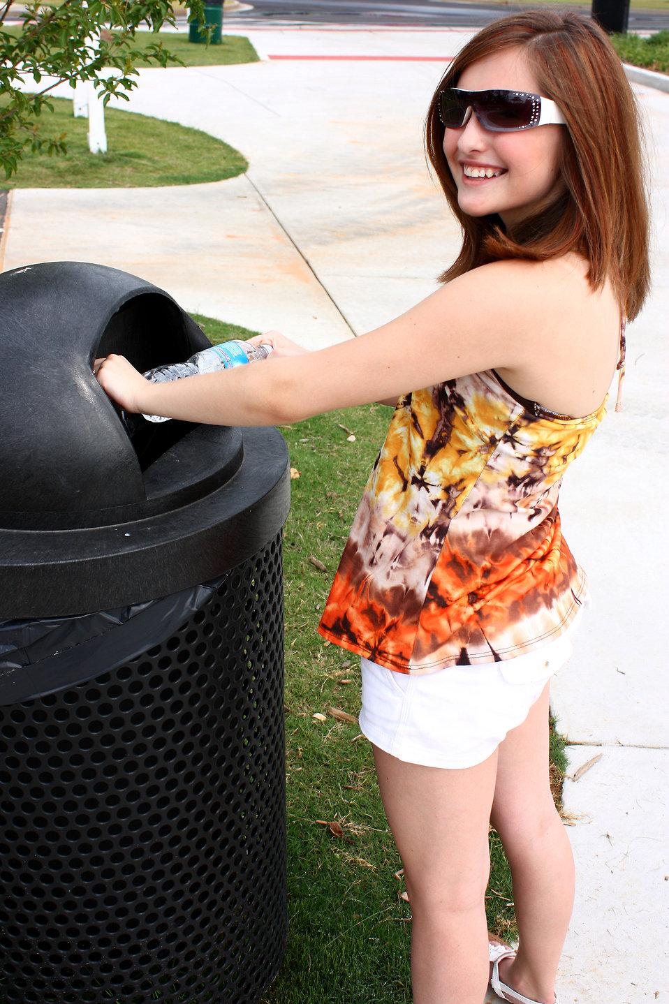 A young girl throwing away trash in a trash can : Free Stock Photo