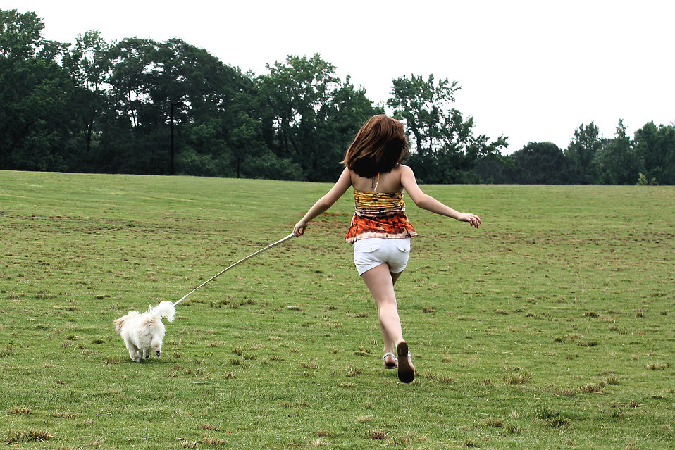 A cute young girl running with her dog.