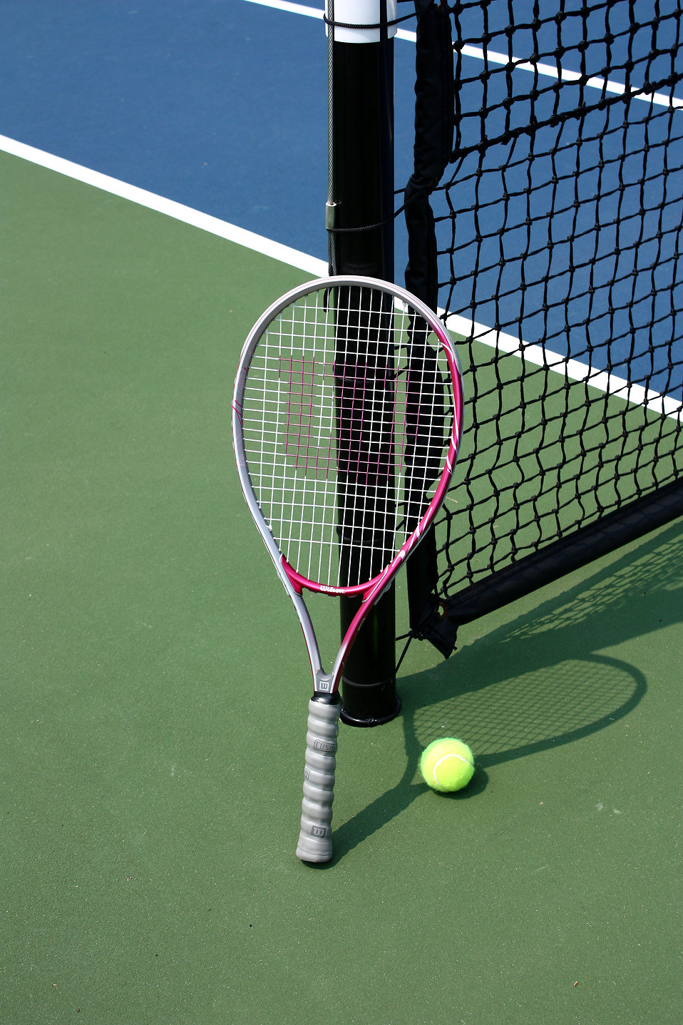 A tennis racquet and ball on a tennis court : Free Stock Photo