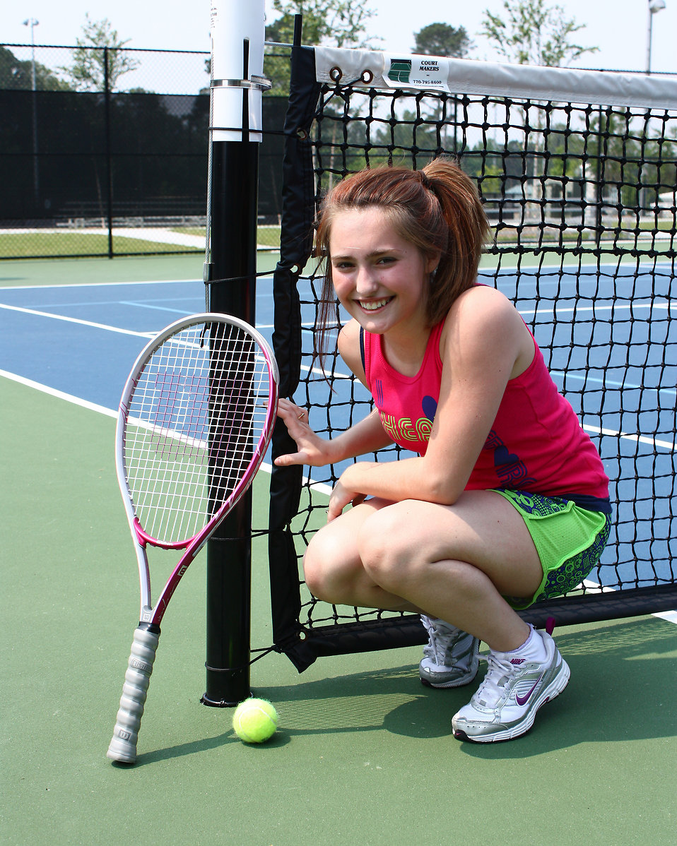 A cute young girl playing tennis.