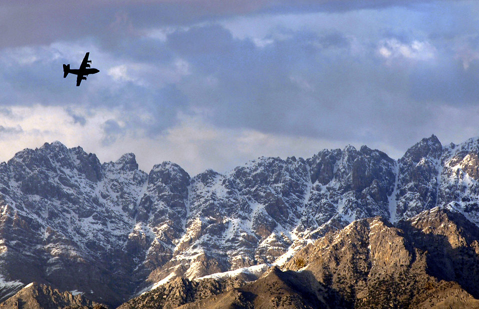 A military airplane flying over mountains : Free Stock Photo