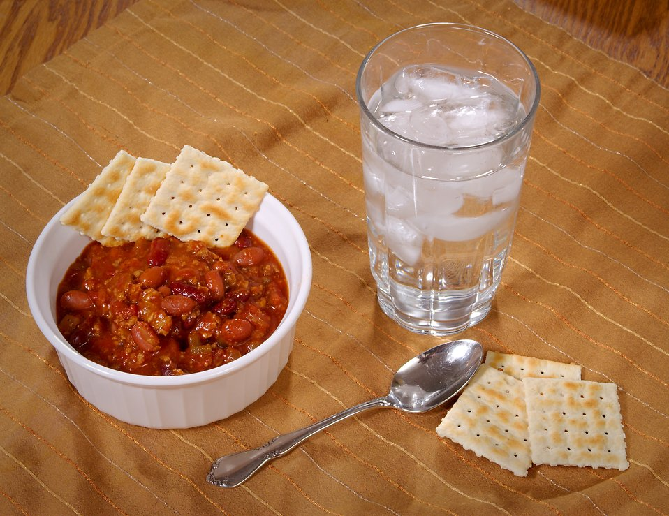 A bowl of beef chili and crackers with a glass of water : Free Stock Photo