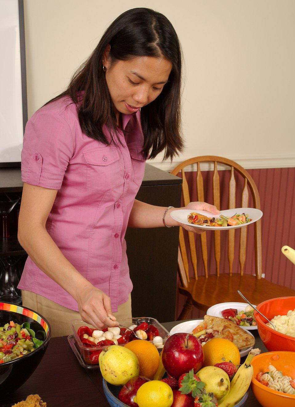 A young Asian woman serving herself food from a table : Free Stock Photo