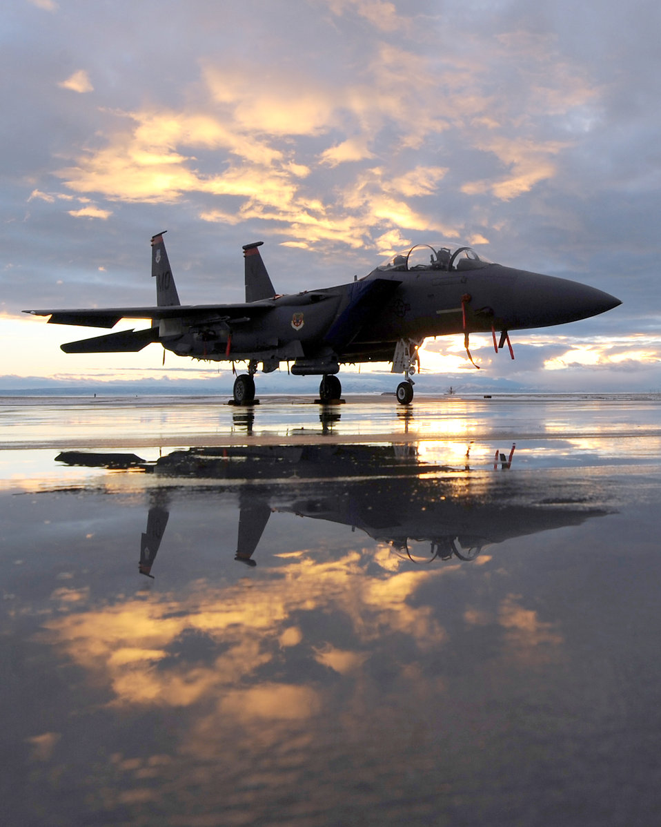 An F-15E fighter jet on a runway at sunset : Free Stock Photo