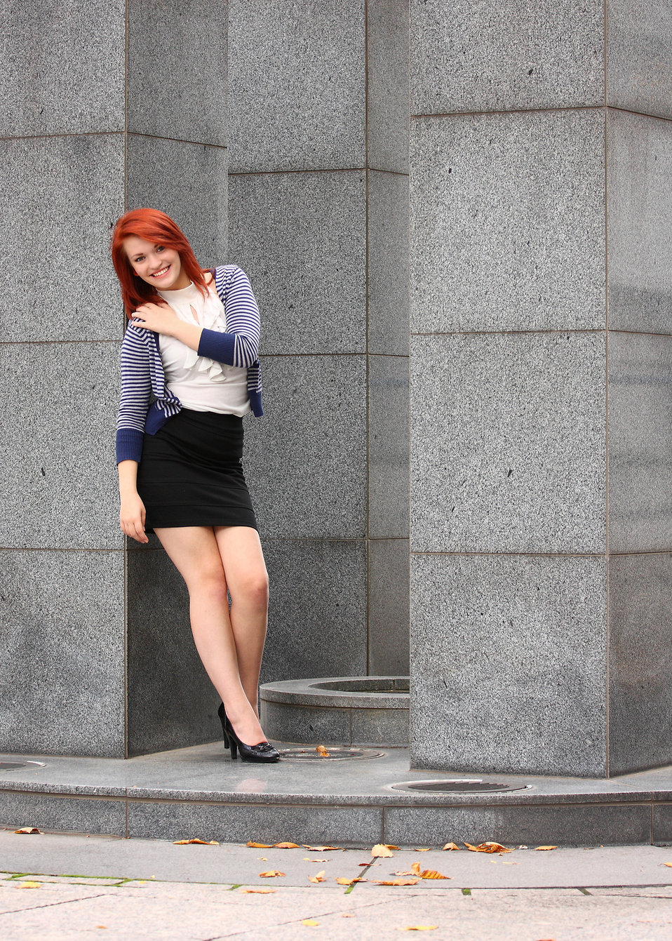 A beautiful young woman dressed in business attire posing near a building.