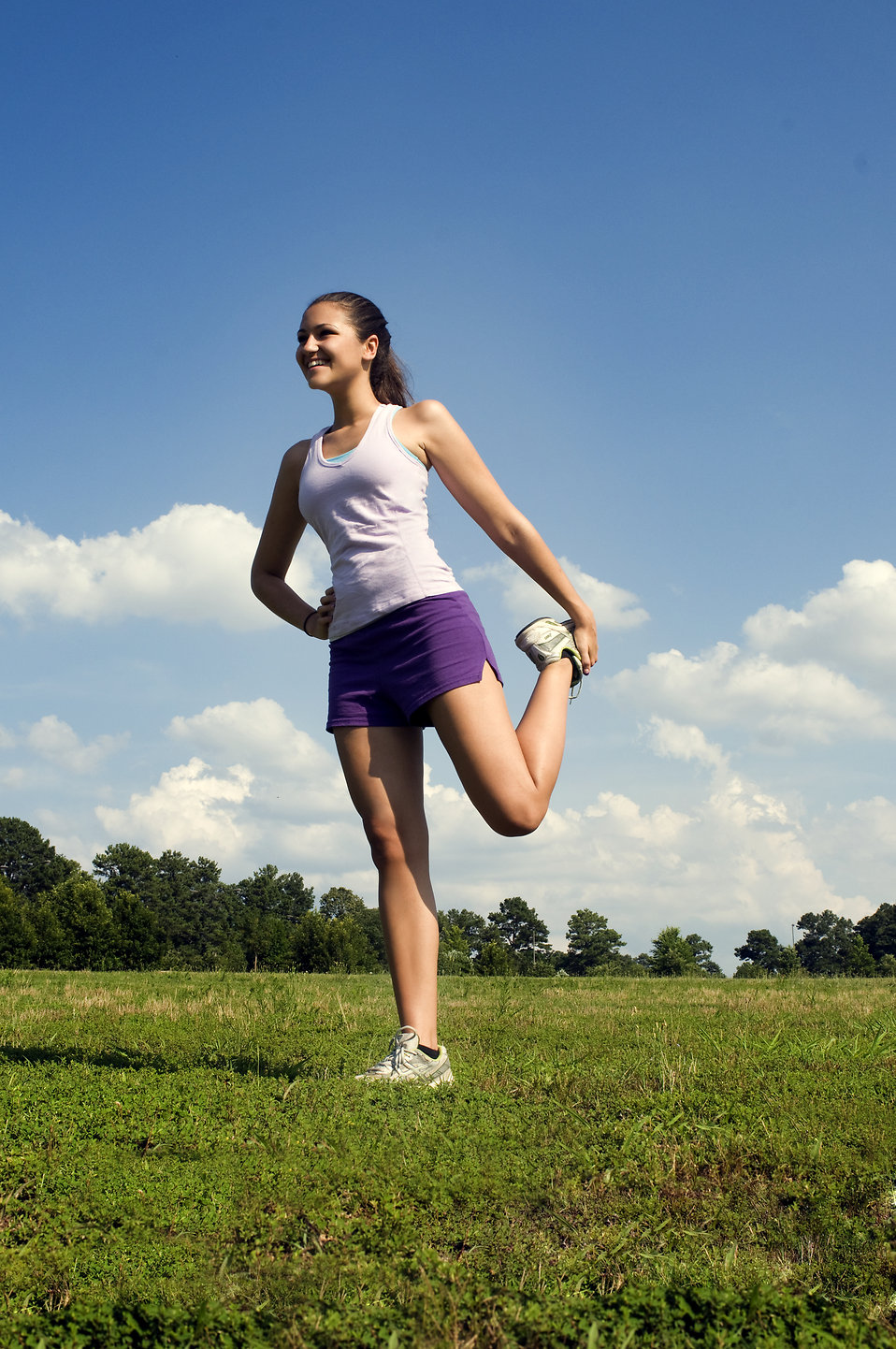 A young woman stretching outdoors before exercising : Free Stock Photo
