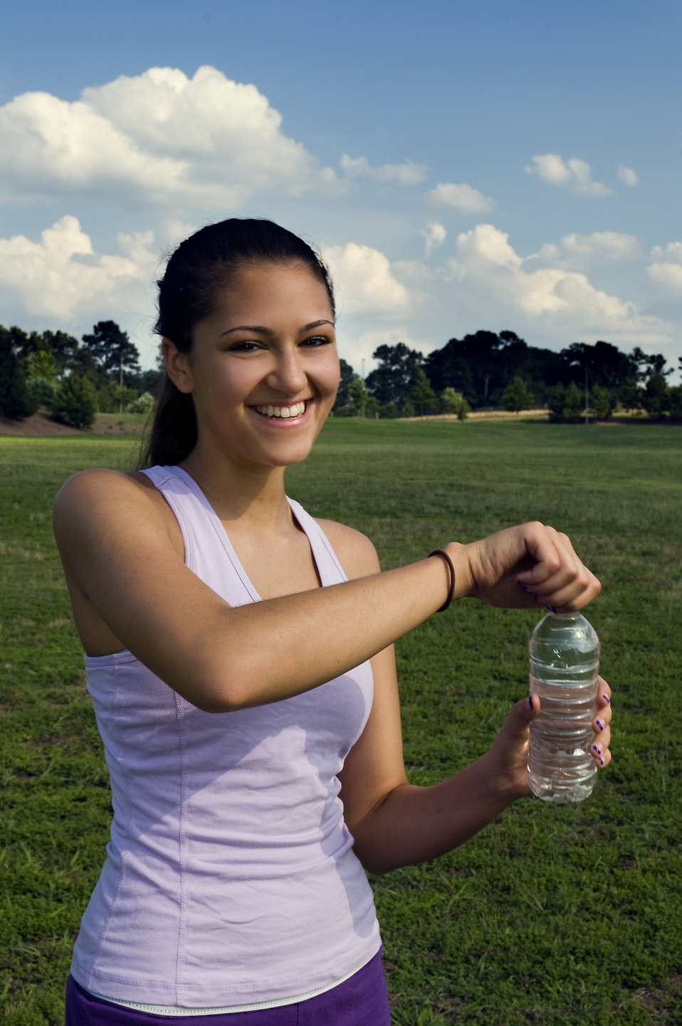 A young woman drinking bottled water outdoors before exercising : Free Stock Photo